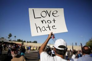 "A demonstrator holds a sign at a ""Freedom of Speech Rally Round II"" across the street from the Islamic Community Center in Phoenix, Arizona May 29, 2015.  Arizona police stepped up security near a mosque on Friday ahead of a planned anti-Islam demonstration featuring displays of cartoons of the Prophet Mohammad, weeks after a similar contest in Texas came under attack from two gunmen.  REUTERS/Nancy Wiechec"